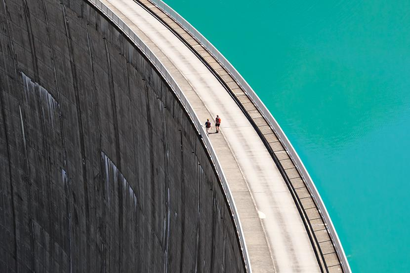people walking on edge of hydrogen dam