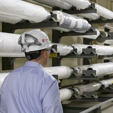 man wearing safety hat walking isle of warehouse rolls of membranes product