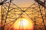 An image of electrical utility towers in front of a sunset.